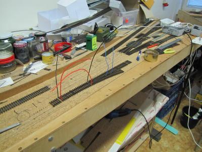 Výhybka připravena k montáži, elektrické přívody jsou připájeny, proběhla kontrola, že všechny vodiče volně pasují do otvorů v podkladu, aniž by rušily polohu a tvar výhybky. .